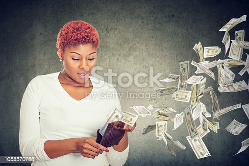 Sad surprised woman looking at her wallet with money dollar banknotes flying out away