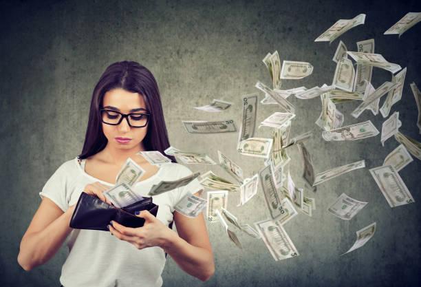 Traurige Frau betrachten ihre Brieftasche mit Geld-Dollar-Banknoten wegfliegen – Foto
