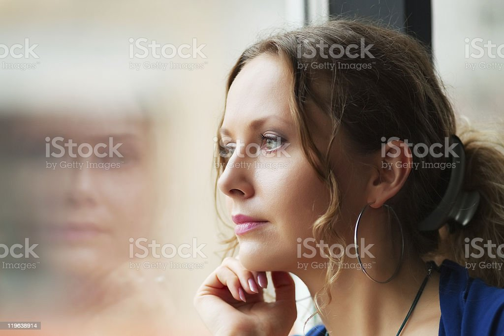 Sad woman looking through the window stock photo