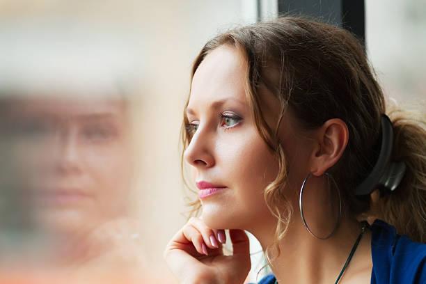 悲しい女性の窓辺 ストックフォト