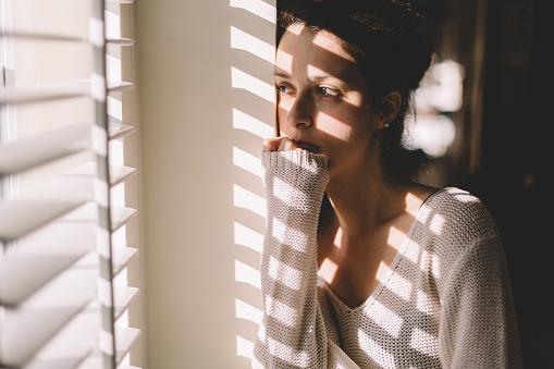 Sad Woman Looking Through The Window Stockfoto en meer beelden van Alleen volwassenen