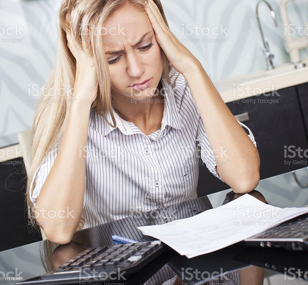 Sad woman looks at the bill Sad woman looks at the bill. Female working at home. Child Makes moms work 25-29 Years Stock Photo