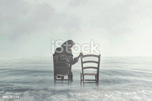 istock sad woman looks nostalgically at her lover's empty chair 890797114