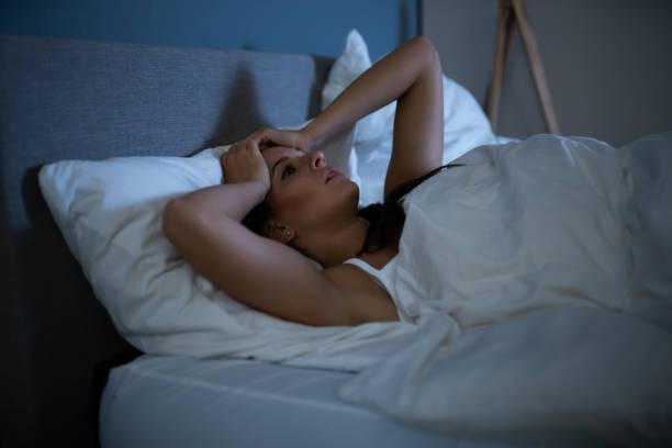 Sad Woman Lying On Bed stock photo