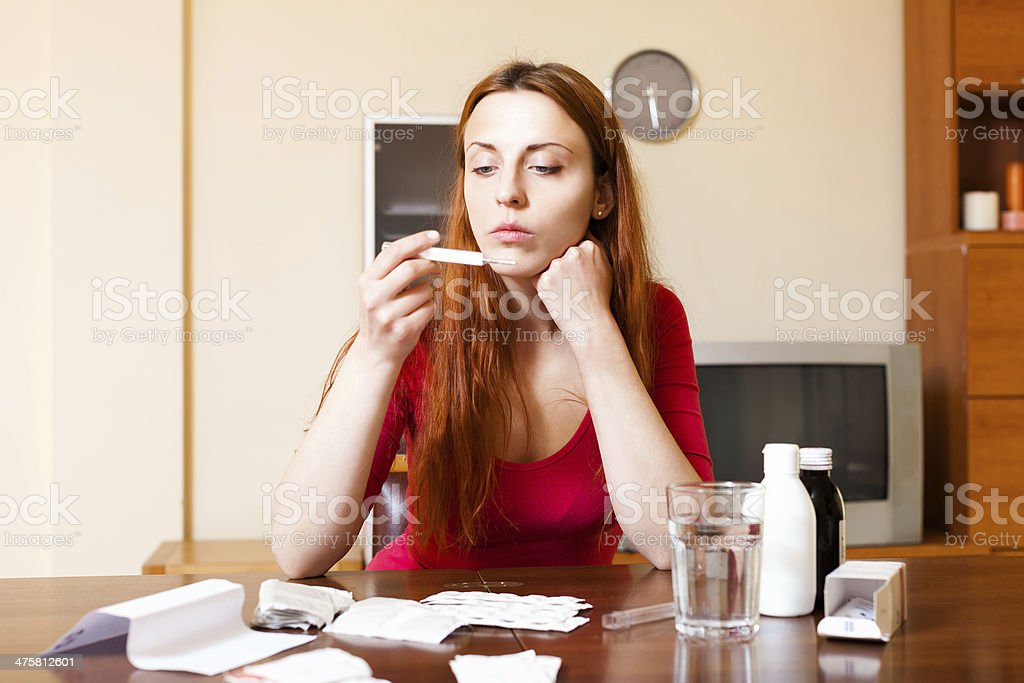 Sad woman measuring temperature with thermometer at home royalty-free stock photo