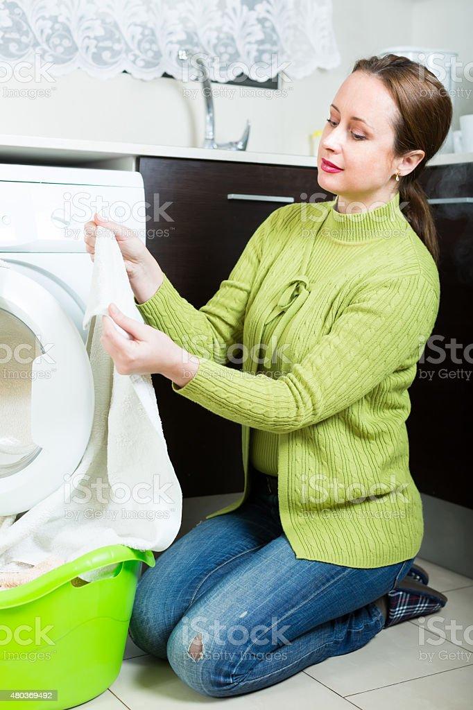 Sad woman near washing machine stock photo
