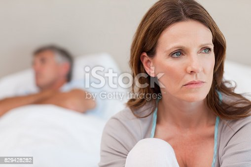 istock Sad woman on bed with her husband in the background 829428282