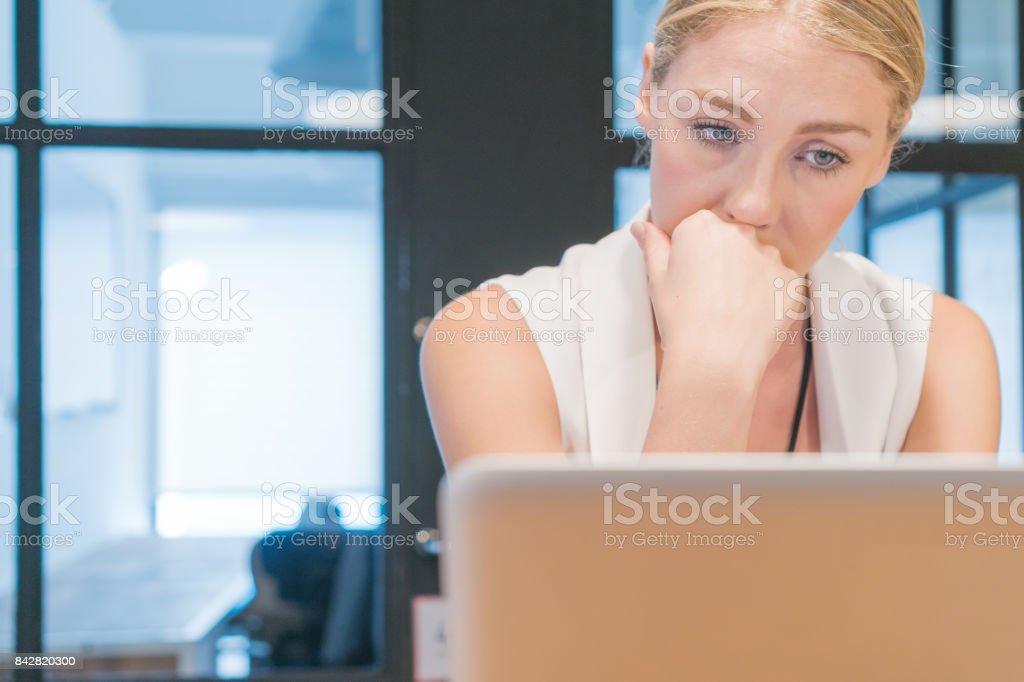 Sad woman on laptop computer stock photo