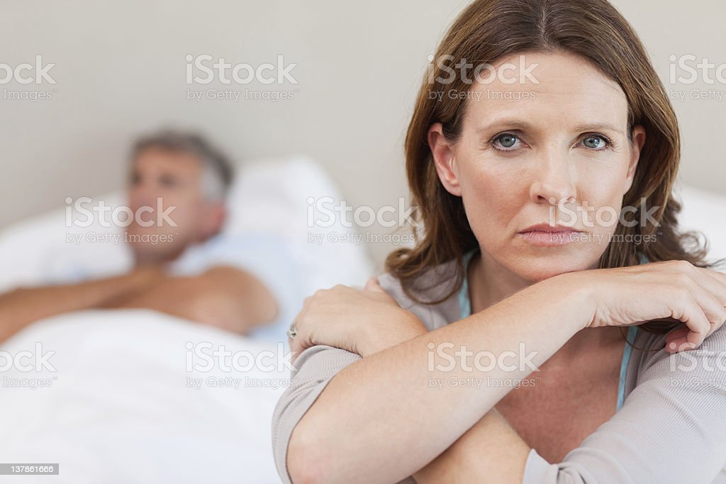Sad woman on the bed with husband in background stock photo