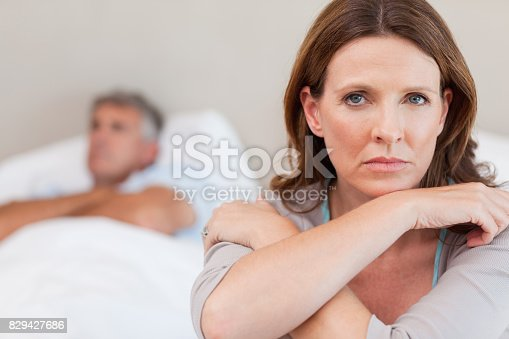 istock Sad woman on the bed with husband in background 829427686