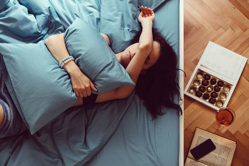Depressed woman in bed with hand on face