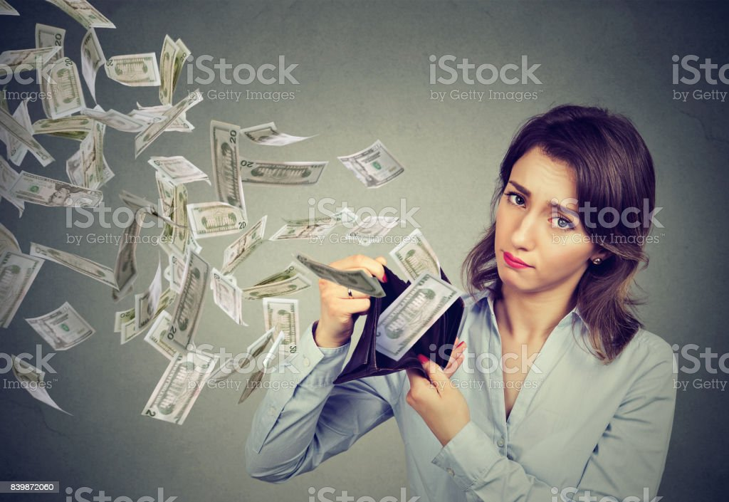 Sad woman showing her wallet with money dollar banknotes flying out away stock photo