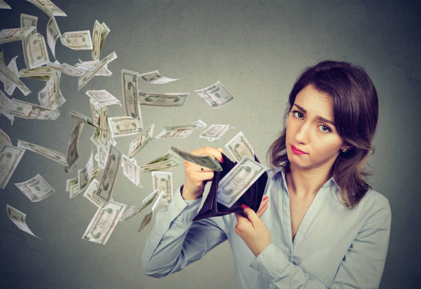sad woman showing her wallet with money dollar banknotes flying out away - attività commerciale foto e immagini stock