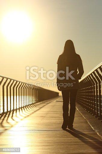 istock Sad woman silhouette walking alone at sunset 493659212