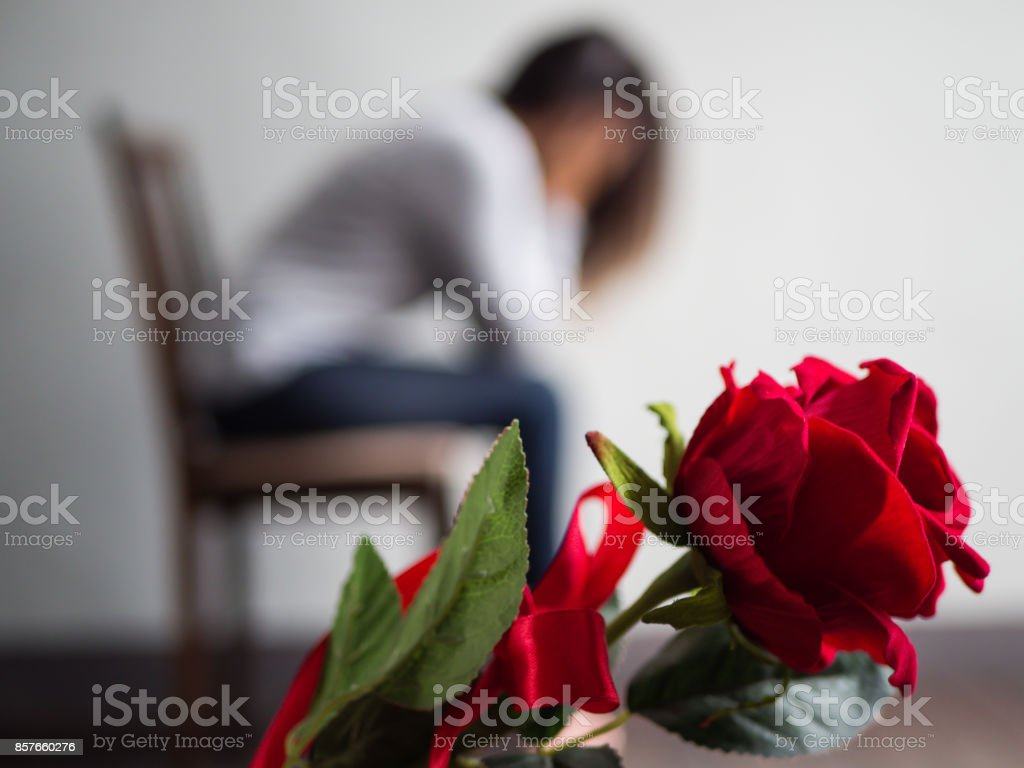 Sad Woman Sitting And Crying With Red Rose In Focus Lonly