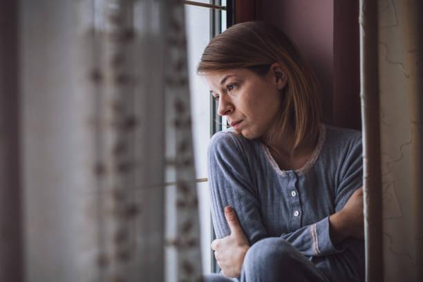 donna triste seduta vicino alla finestra a guardare fuori - assuefazione foto e immagini stock