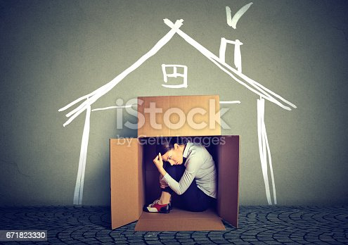 istock Sad woman sitting in a box house in search for shelter 671823330