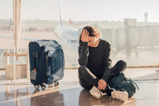Sad (tired) woman sitting in the airport - missed or cancelled flight concept. Sad (tired) woman sitting in the airport - missed or cancelled flight concept. jet lag stock pictures, royalty-free photos & images