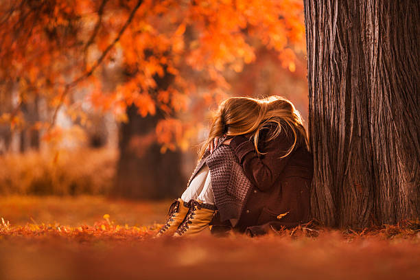 Sad woman sitting in the park during autumn day. stock photo