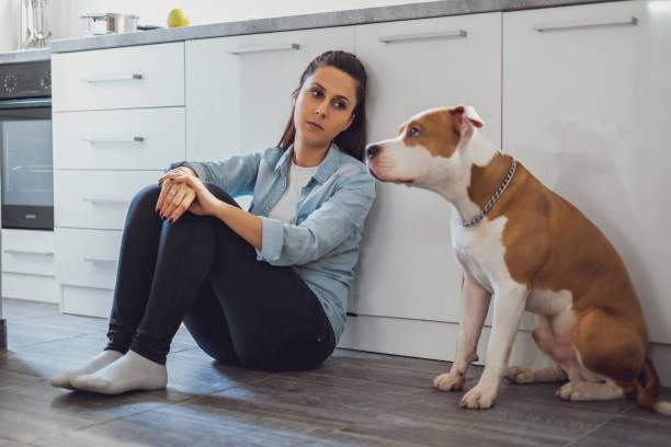 Triste mujer sentada en un piso de la cocina con su perro - foto de stock