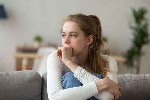 istock Sad woman sitting on couch alone at home 1063392694