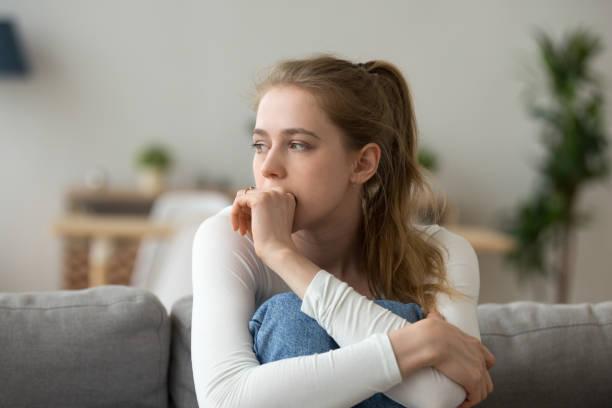 悲傷的女人獨自坐在沙發上在家裡 - 年輕女性 個照片及圖片檔