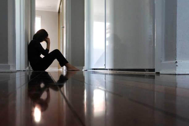 Sad woman sitting on dark home corridor floor. Sad adult woman sitting on dark home corridor floor. despair stock pictures, royalty-free photos & images