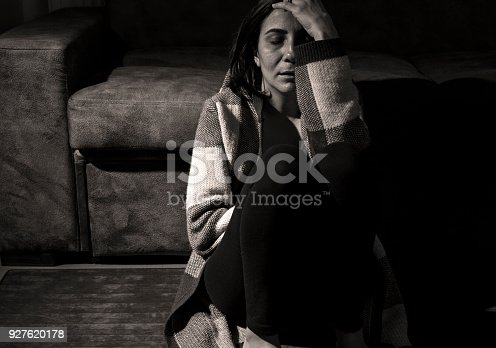 istock Sad Woman Sitting On Floor In Dark Room 927620178