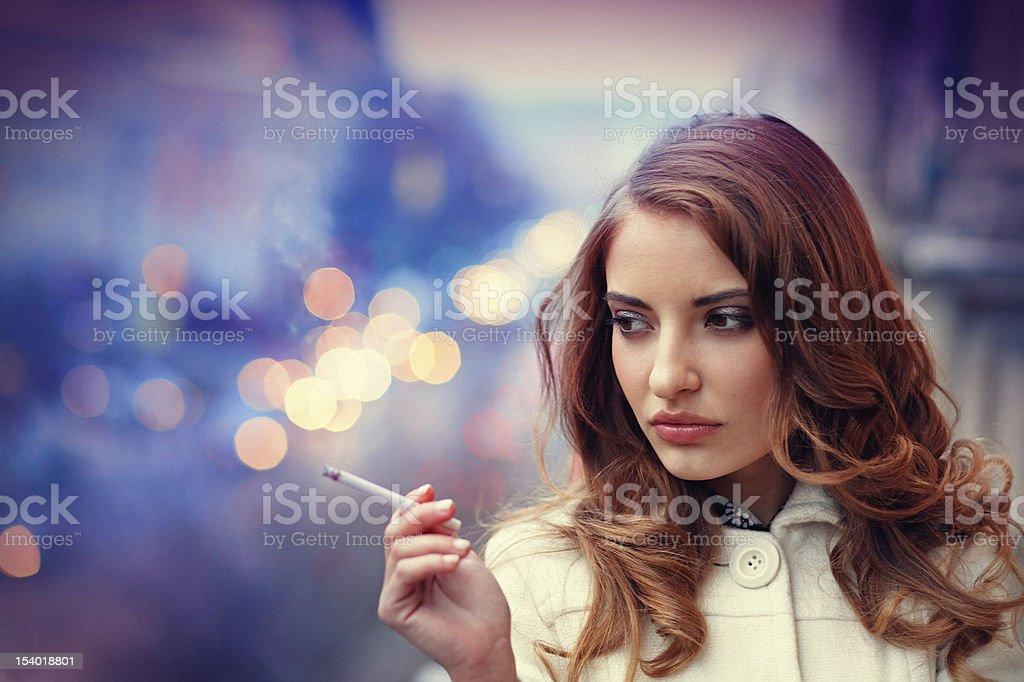 sad woman smonking cigarette on the balcony stock photo