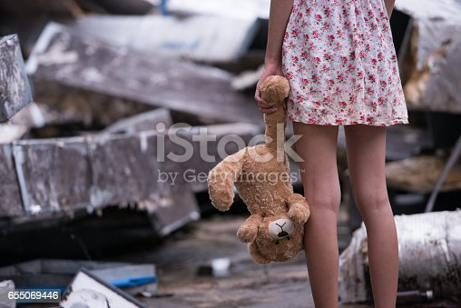 istock Sad woman standing with doll 655069446