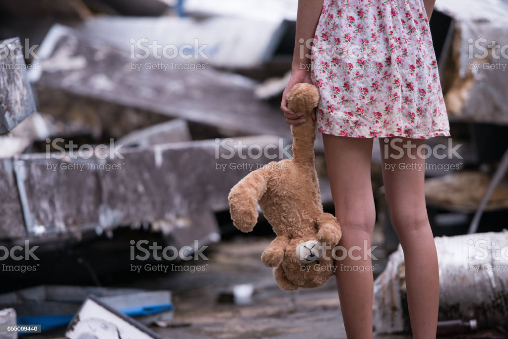 Sad woman standing with doll stock photo