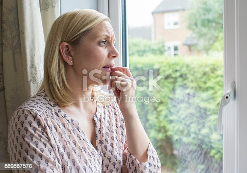 543048812 istock photo Sad Woman Suffering From Agoraphobia Looking Out Of Window 889587576