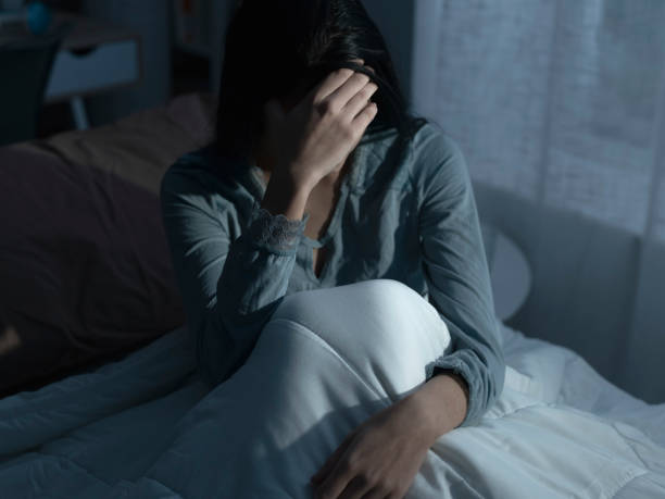 Sad woman suffering from insomnia in her bed stock photo