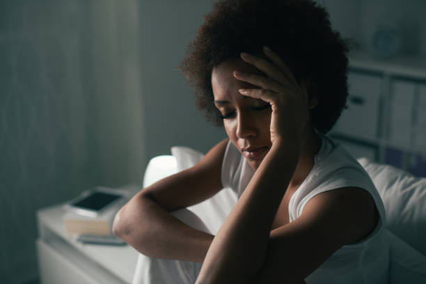 Sad woman suffering from insomnia Sad depressed woman suffering from insomnia, she is sitting in bed and touching her forehead, sleep disorder and stress concept headache stock pictures, royalty-free photos & images