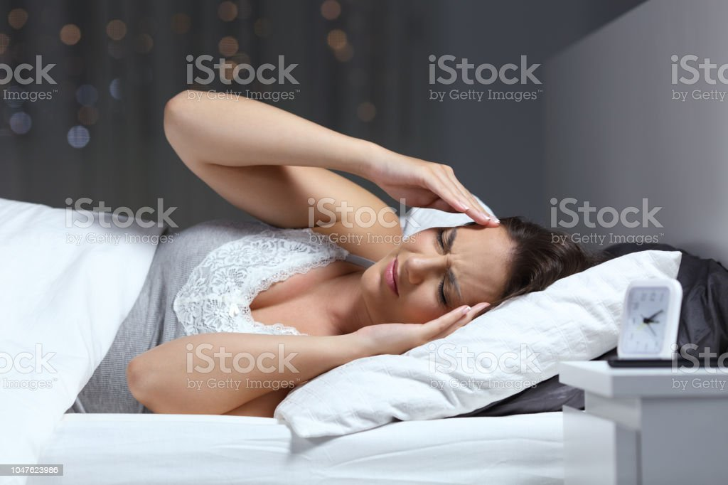 Sad woman suffering migraine in the bed in the night stock photo