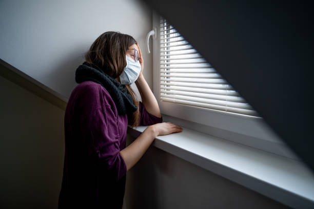sad woman trapped in quarantine looking trough window daydreaming about going outdoors - stock photo - trap house stock pictures, royalty-free photos & images