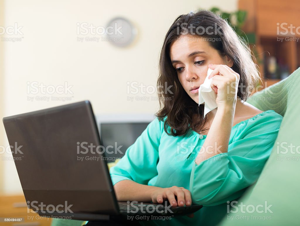 Sad  woman  using  laptop - Royalty-free Adult Stock Photo