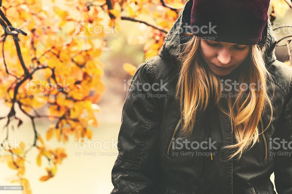 Sad Woman walking in park with autumn leaves on background – Foto