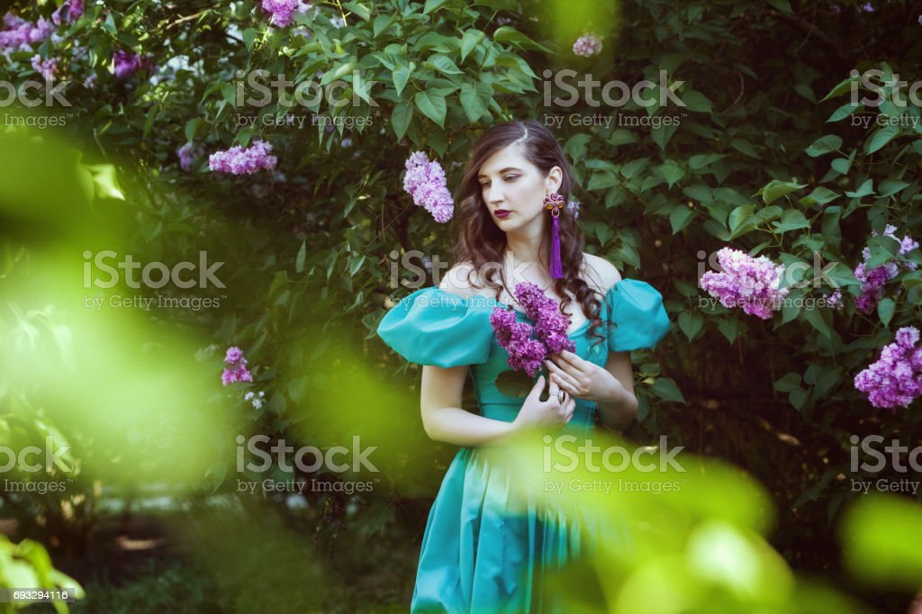 Sad woman with a branch of lilac. stock photo