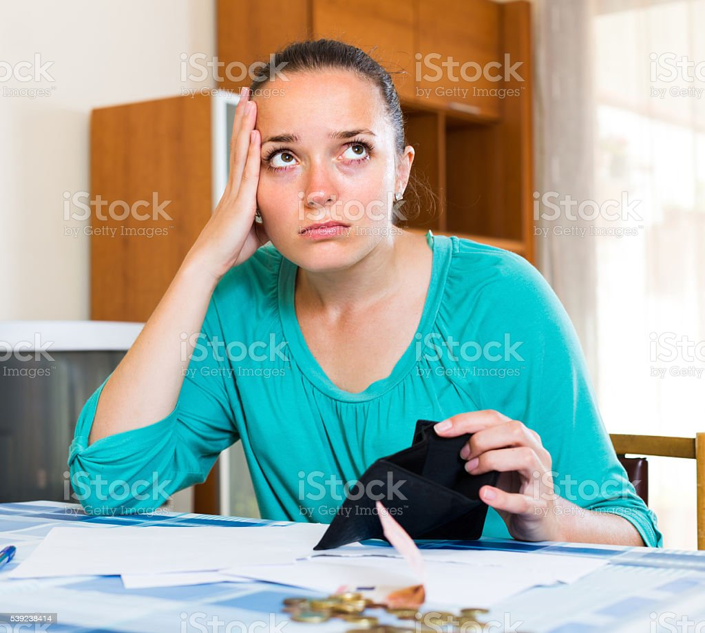 Sad woman with bills at the table royalty-free stock photo