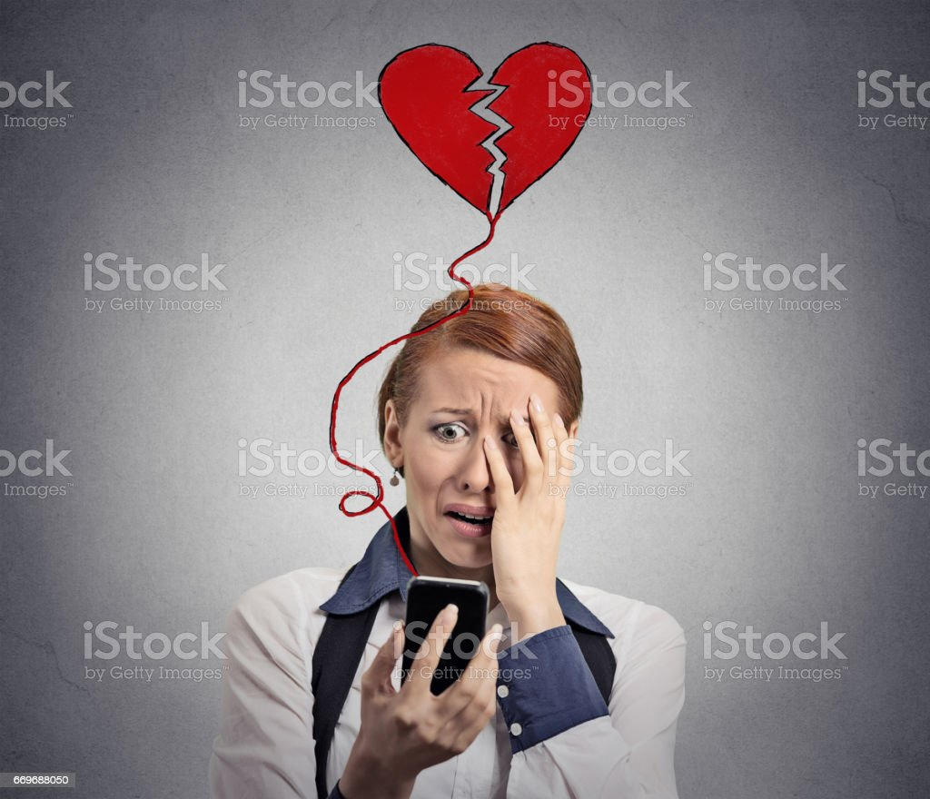 Sad woman with broken heart looking at her mobile phone stock photo