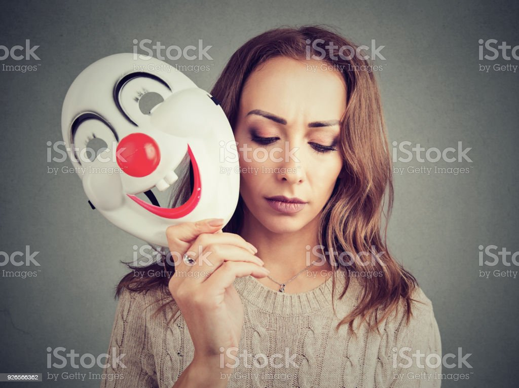 Sad woman with clown mask stock photo