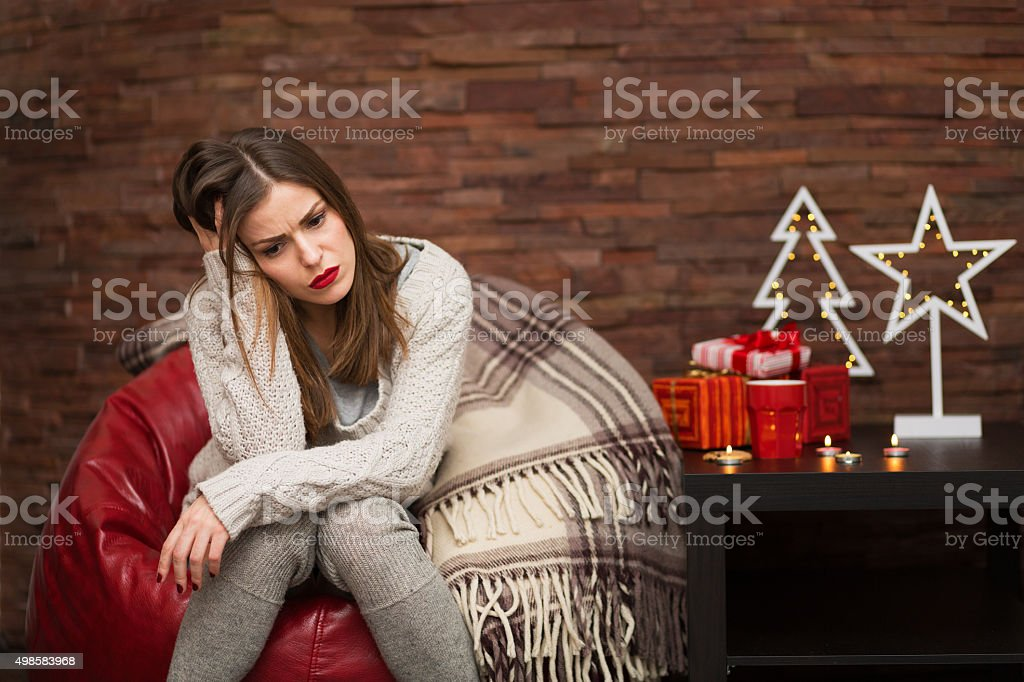 Sad woman with gift boxes Sad young woman with Christmas presents at her home 2015 Stock Photo
