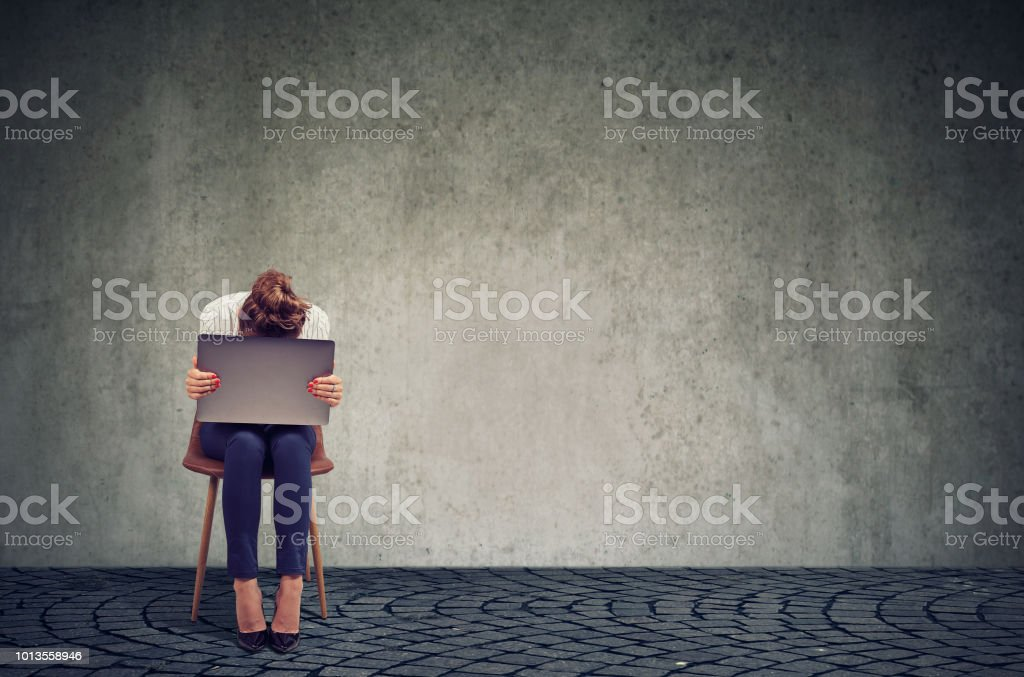 Traurige Frau mit Laptop auf Stuhl – Foto