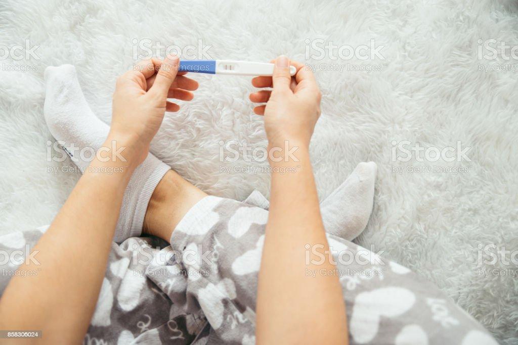 sad woman with pregnancy test stock photo