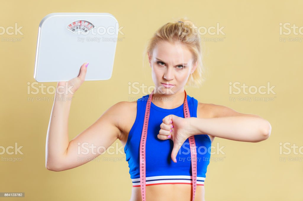 Sad woman with weight gain thumb down sign royalty-free stock photo