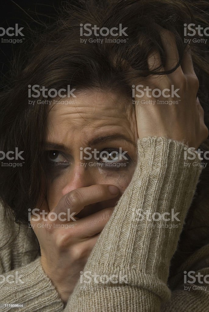 Sad woman's face with smeared makeup covering her mouth royalty-free stock photo