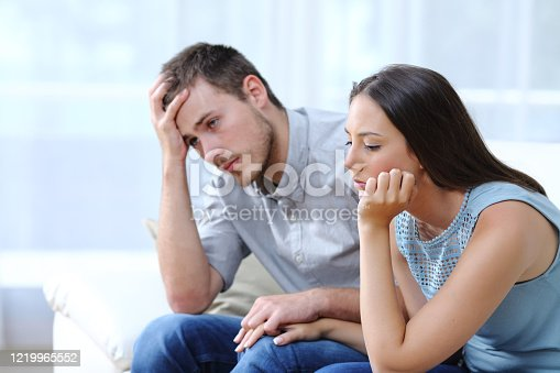 istock Sad worried couple complaining on a couch at home 1219965552