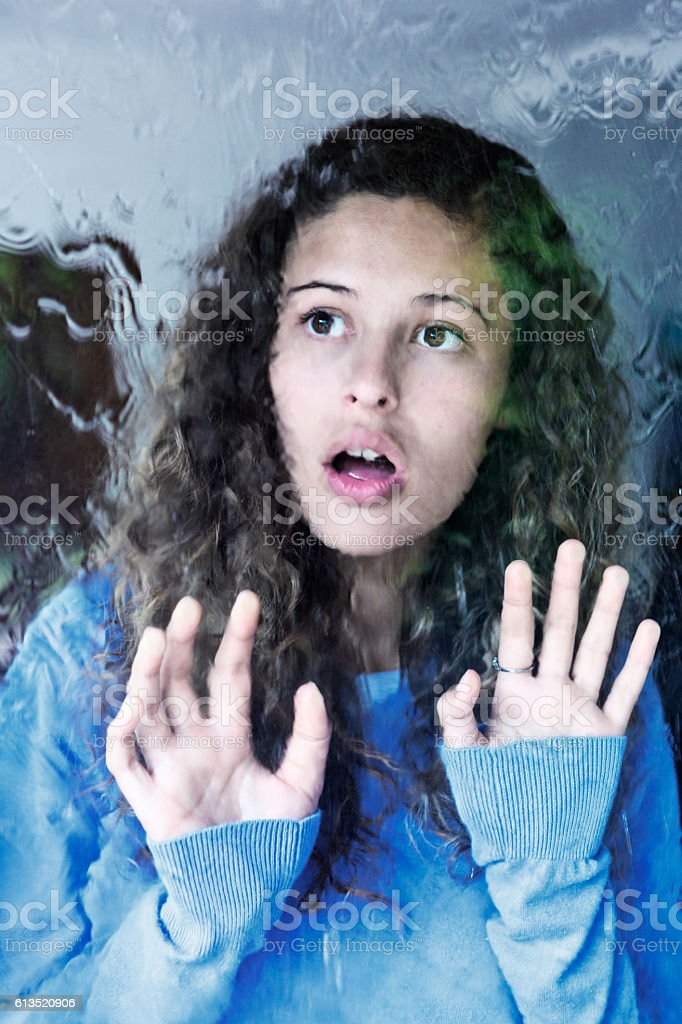 Sad young beauty touching window looks out at rain stock photo