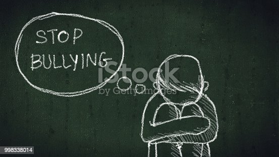 istock sad young boy sitting on the floor with text stop bullying written with chalk on chalkboard. social problems of humanity 998338014